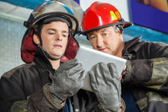 Male Firefighters Using Digital Tablet At Fire. Low angle view of male firefighters using digital tablet at fire station Stock Photography