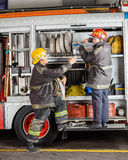 Male Firefighters Working At Truck Royalty Free Stock Photography