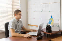 Male Firm Manager Using Laptop at His Desk Stock Image