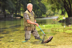 Male fisherman catching fish with net in a river. On a sunny summer day stock photography