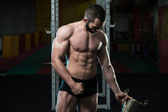 Male Fitness Competitor Showing His Winning Medal. Bodybuilder Competitor Showing His Winning Medal - Male Fitness Competitor Showing His Winning Medal Royalty Free Stock Image