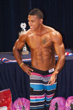 Male fitness contestant shows his best physique on stage Stock Images
