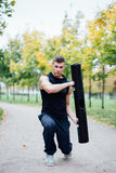 Male fitness doing exercise lunge with vipr, morning workout in the park. Royalty Free Stock Photography