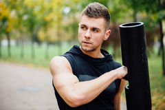 Male fitness doing exercise lunge with vipr, morning workout in the park. Stock Photo