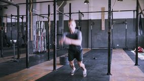 Male fitness instructor showing squat exercise at modern plase. Male fitness instructor showing jumping exercise at loft plase. Jumping squats at gym. Effective stock video footage