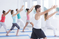 Male fitness instructor with students. Handsome male fitness instructor practicing stretch and yoga exercises with students Royalty Free Stock Image