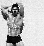 Male fitness model. Sexy fine art black and white portrait of a very muscular shirtless male model posing with arms up Royalty Free Stock Images