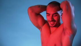 Sexy Muscular Bodybuilder Man Shirtless In Studio. Male Fitness Model Flexing muscles, isolated on blue background. Studio shot stock video