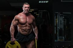 Strong mature man with relief body posing in gym royalty free stock photo