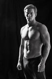 Male fitness model showing muscles in studio. With a black background Royalty Free Stock Photos