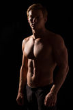 Male fitness model showing muscles in studio Royalty Free Stock Images