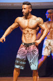 Male fitness model shows his physique in swimsuit om stage Royalty Free Stock Image
