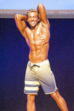 Male fitness model shows his physique in swimsuit om stage Royalty Free Stock Images