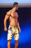Male fitness model shows his physique in swimsuit om stage. MAASTRICHT, THE NETHERLANDS - OCTOBER 25, 2015: Male physique model shows his best front pose at Stock Images