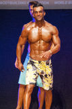 Male fitness model shows his physique in swimsuit om stage. MAASTRICHT, THE NETHERLANDS - OCTOBER 25, 2015: Male physique model shows his best front pose at Stock Photos
