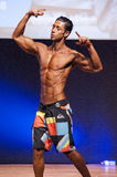 Male fitness model shows his physique in swimsuit om stage Royalty Free Stock Photography