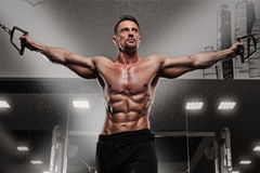 Male fitness model working out on simulator Stock Images