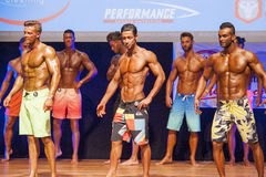 Male fitness models show their physique in swimsuit om stage Royalty Free Stock Images