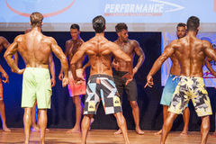 Male fitness models show their physique in swimsuit om stage Royalty Free Stock Photo