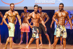 Male fitness models show their physique in swimsuit om stage Stock Photos