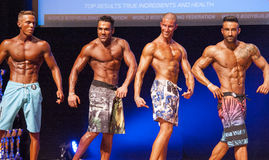 Male fitness models show their physique in swimsuit om stage Stock Photography