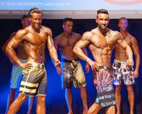 Male fitness models show their physique in swimsuit om stage Royalty Free Stock Photography