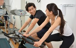 Male Fitness Trainer Assisting a Young Female Student Doing Exer Royalty Free Stock Image