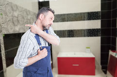 Male fitter pointing finger behind him. Male fitter pointing finger or indicate something behind him while sitting in the bath room with advertising area Stock Photos