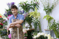 Male florist in apron standing in flower shop, leaning on broom beside display, smiling, portrait Royalty Free Stock Photos
