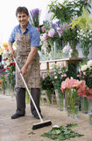 Male florist in apron standing in flower shop, sweeping floor with broom, smiling, portrait Royalty Free Stock Images