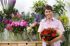 Male florist with bouquet of flowers, smiling, portrait Stock Image