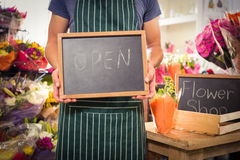 Male florist holding open sign on slate at his flower shop Royalty Free Stock Images