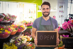 Male florist holding open sign on slate at his flower shop Stock Image