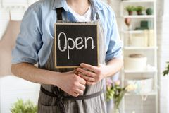 Male florist holding OPEN sign. At workplace Royalty Free Stock Photo