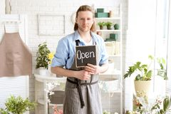 Male florist holding OPEN sign. At workplace Stock Images