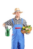 Male florist holding a watering can and flowers Royalty Free Stock Photos