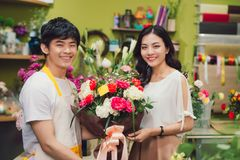 Male florist offering flowers at the counter in the florist shop.  Stock Photo