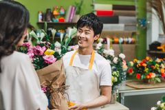 Male florist offering flowers at the counter in the florist shop.  Royalty Free Stock Photography