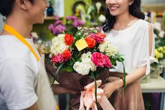 Male florist offering flowers at the counter in the florist shop Stock Photography