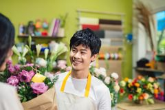 Male florist offering flowers at the counter in the florist shop Stock Image