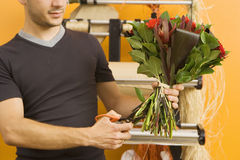 Male florist preparing bouquet of flowers in flower shop, cutting stems with scissors, mid-section Royalty Free Stock Photos
