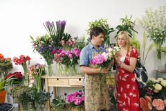 Male florist serving woman beside display in flower shop, holding bunch of flowers, woman choosing Stock Photography