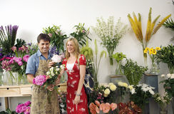 Male florist serving woman in flower shop, holding bunch of flowers, smiling, display in background Royalty Free Stock Photo