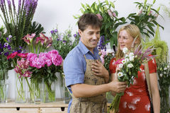 Male florist serving woman in flower shop, holding bunch of white flowers, smiling Stock Photos