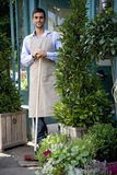 Male florist standing with a  broom outside his shop Royalty Free Stock Photography