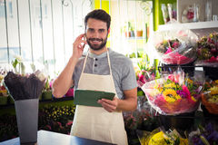 Male florist talking on mobile phone while holding file. Portrait of male florist talking on mobile phone while holding file at his flower shop Stock Photos