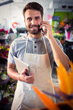 Male florist talking on mobile phone. Portrait of male florist talking on mobile phone at his flower shop Royalty Free Stock Image