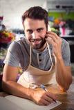 Male florist talking on mobile phone. Portrait of male florist talking on mobile phone at his flower shop Stock Images