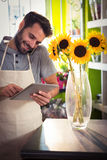 Male florist talking on mobile phone while using digital tablet. At his flower shop Stock Images