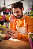 Male florist talking on mobile phone while using digital tablet. At his flower shop Royalty Free Stock Images